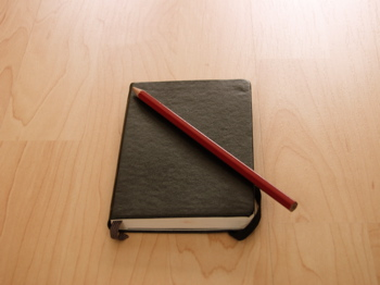 A Modo & Modo Moleskine, black sketchbook. A red pencil lies on top of it.